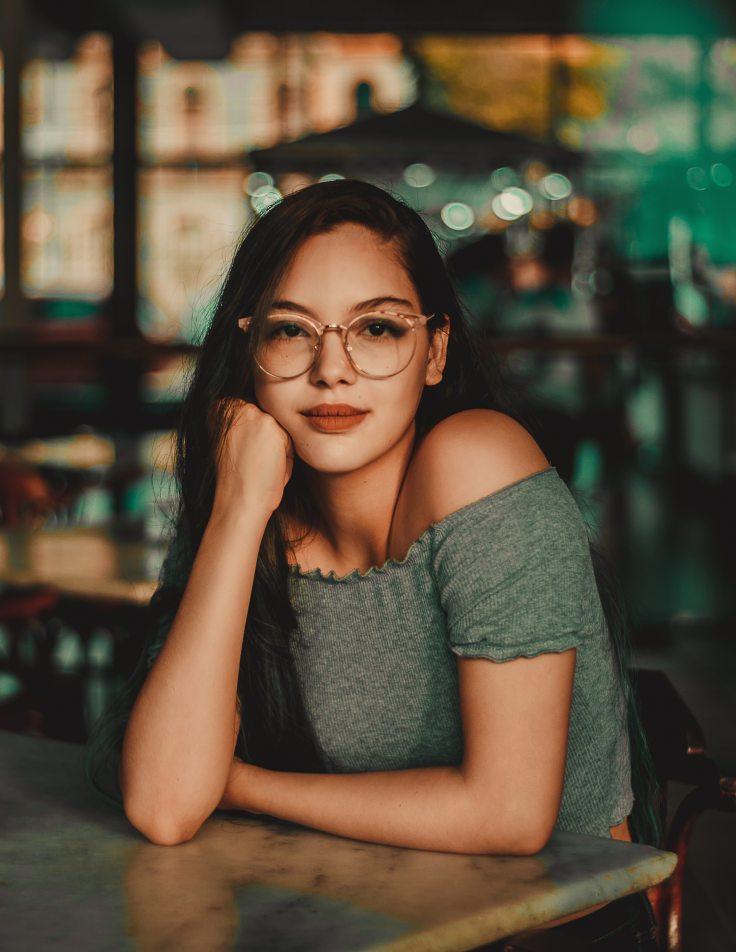 woman-wearing-eyeglasses-sitting-beside-table-1998865